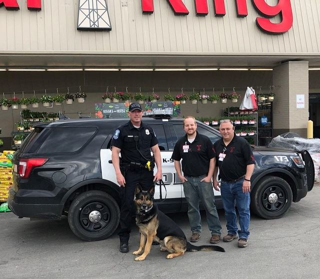 Image of Officer Nist with Bear the dog in front of Rural King store